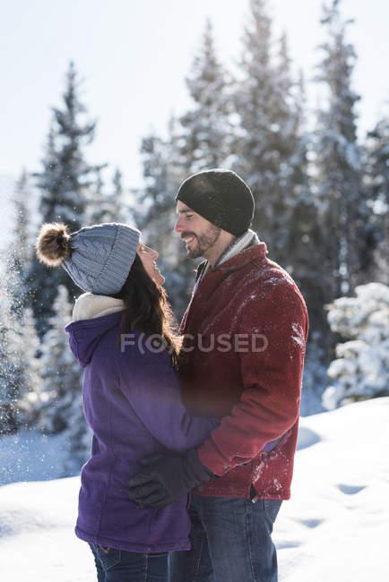 Paar umarmt und sahen einander im winterlichen Wald. — Stockfoto