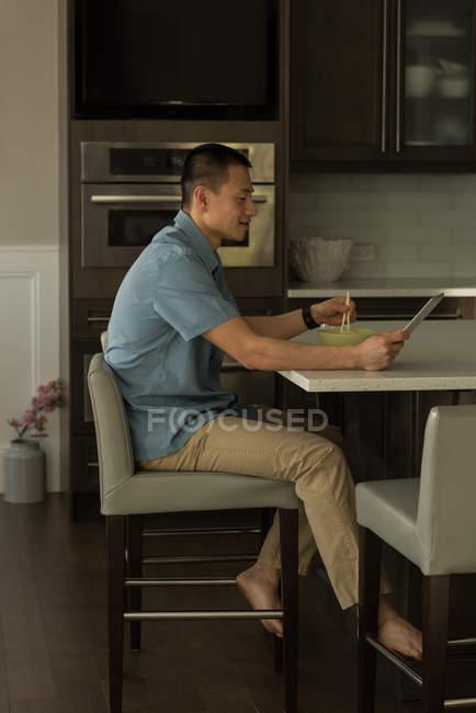 Человек, использующий цифровой планшет во время завтрака дома — стоковое фото
