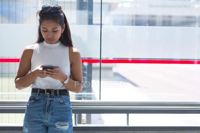 Використання мобільного телефону на автобусній зупинці дівчинки-підлітка — стокове фото