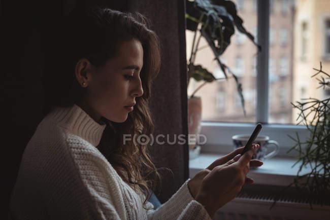 Close-up de mulher bonita usando seu telefone celular em casa — Fotografia de Stock