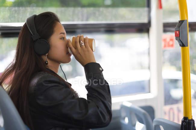 Vista lateral da menina adolescente tomando café no ônibus — Fotografia de Stock