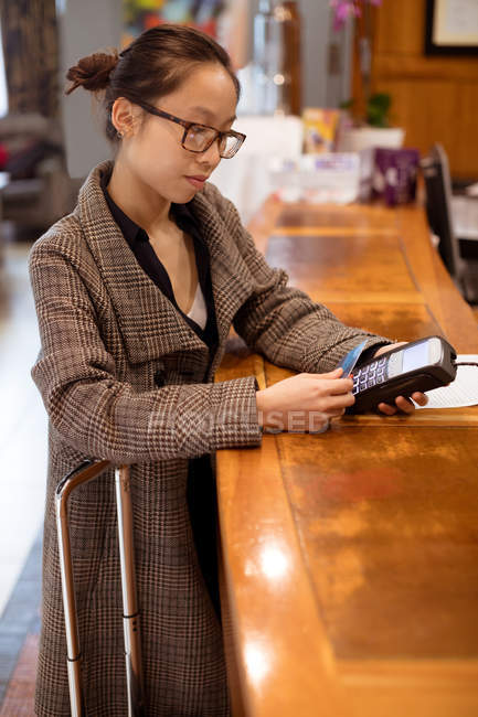 Woman executive swiping his card on payment terminal machine at reception area — Stock Photo