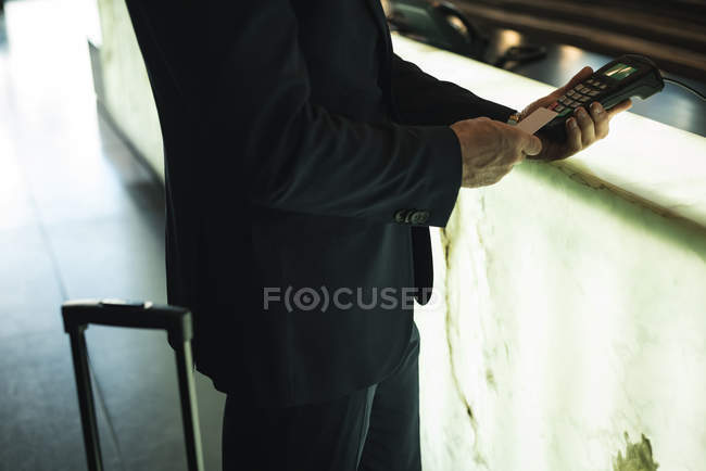 Cropped image of Businessman swiping his card on payment terminal machine in hotel — Stock Photo