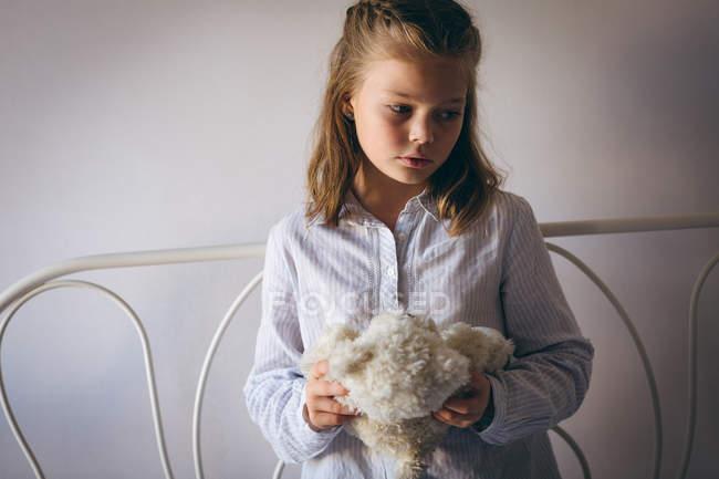 Грустная девушка держит плюшевого мишку дома — стоковое фото