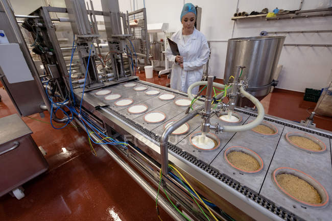 Female worker monitoring food near production line in the