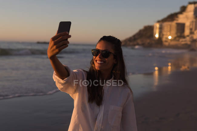 Donna che cattura selfie con il telefono cellulare alla spiaggia al crepuscolo. — Foto stock
