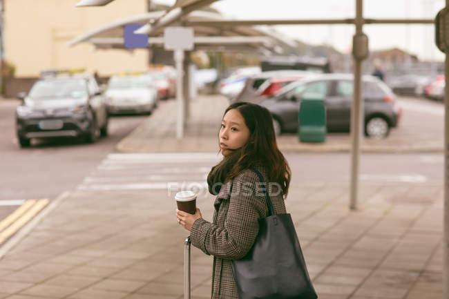 Жінка з багажем стояти під таксі — стокове фото
