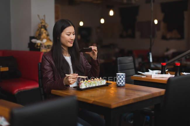 Принимая фото женщина еды с мобильного телефона в ресторане — стоковое фото