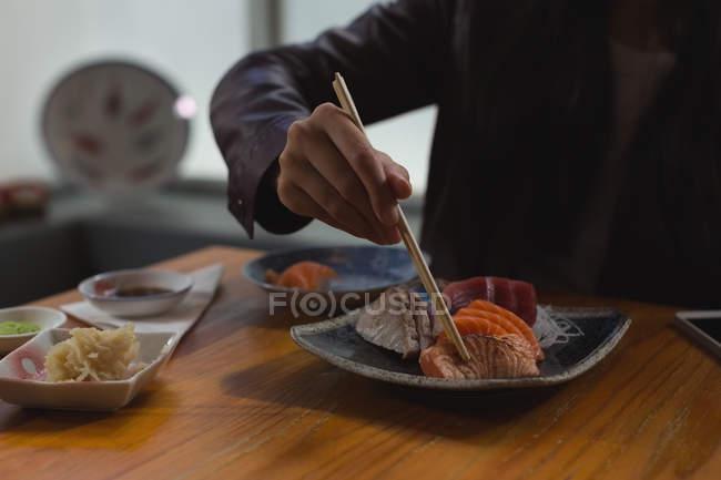 Середине раздел женщины, имеющие суши еда в ресторане — стоковое фото