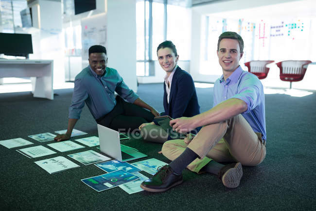Male and female executives discussing over graphs and laptop in office — Stock Photo