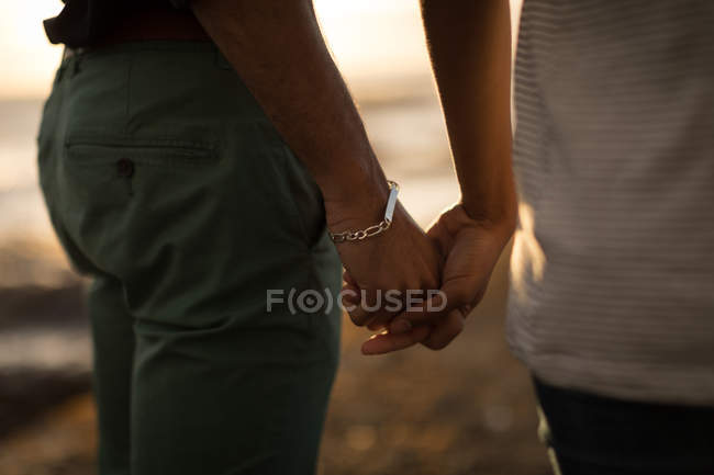 Mid section of romantic couple holding hand in a beach during sunset — Stock Photo