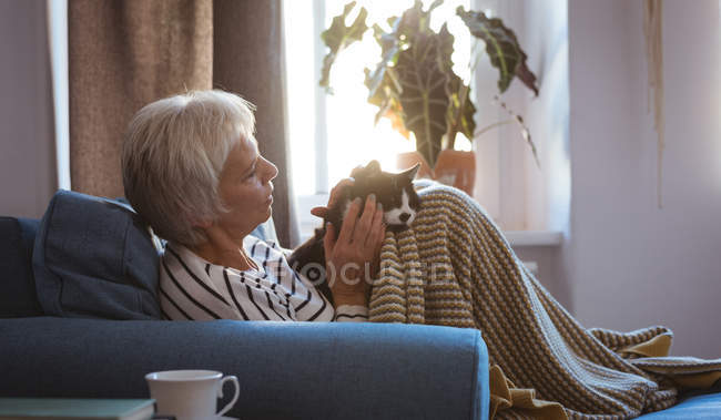 Senior woman relaxing on sofa stroking her cat in living room at home — Stock Photo