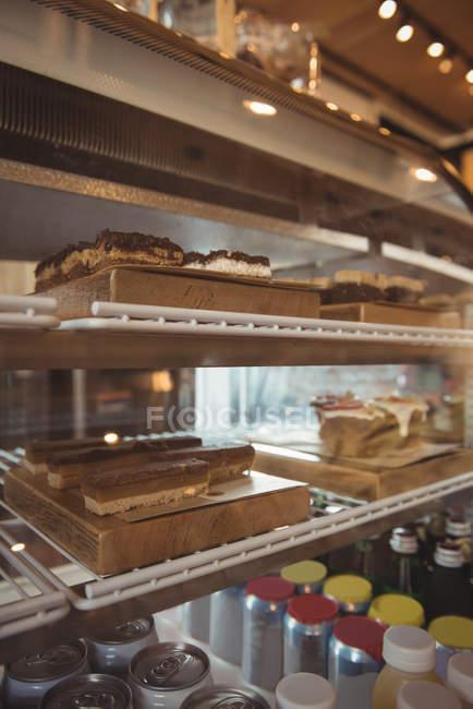 Variedade de bolos e garrafas em exposição no café — Fotografia de Stock