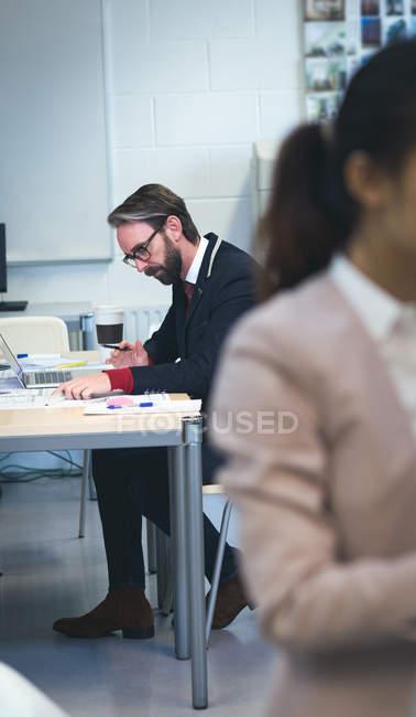 Executive lavora su laptop in ufficio moderno — Foto stock