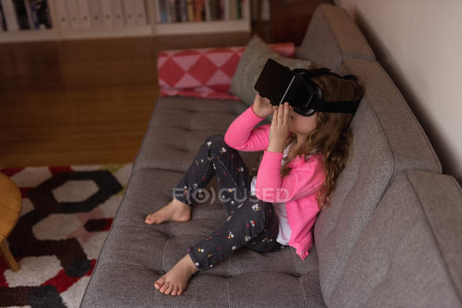 Girl using virtual reality headset on sofa in living room at home — Stock Photo