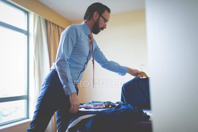 Kluger Geschäftsmann wählt Blazer im Hotelzimmer — Stockfoto