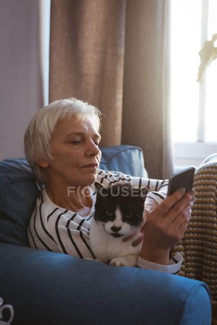 Крупный план пожилой женщины, сидящей на диване со своей кошкой, используя мобильный телефон в гостиной дома — стоковое фото