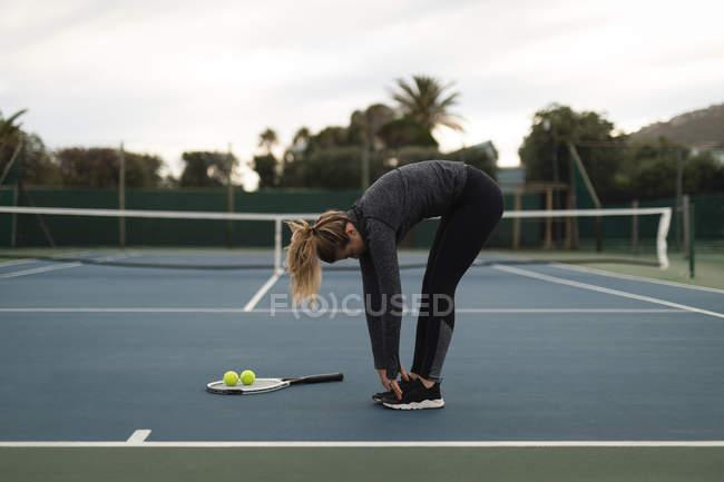 Jovem se exercitando na quadra de tênis — Fotografia de Stock