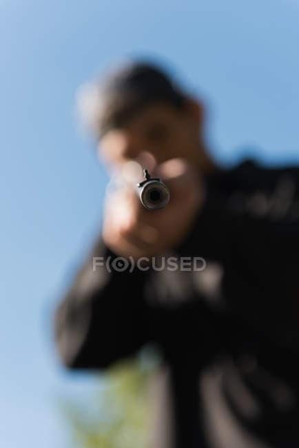 Embaçado homem apontando o rifle sniper no alvo no tiro ao alvo — Fotografia de Stock