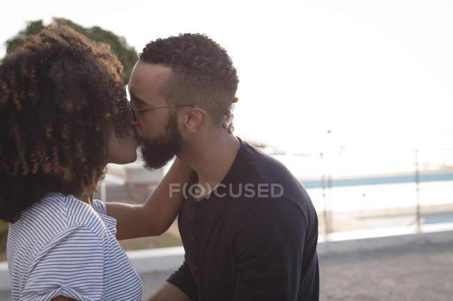 Romántica pareja besándose cerca de la playa en un día soleado - foto de stock