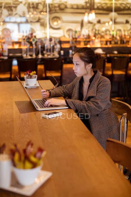 Executivo feminino usando laptop à mesa no hotel — Fotografia de Stock
