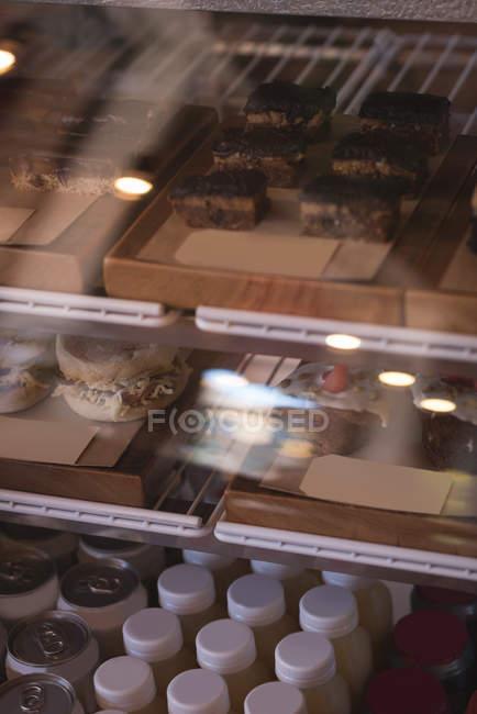 Variedade de comida saborosa e garrafas em exposição no café — Fotografia de Stock