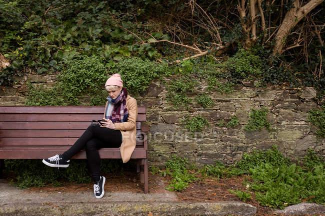 Женщина сидит на скамейке и с помощью мобильного телефона в парке — стоковое фото