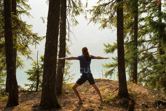 Fit man performing stretching exercise in a lush green forest at the time of dawn — Stock Photo