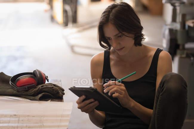 Female artisan using digital tablet in workshop. — Stock Photo