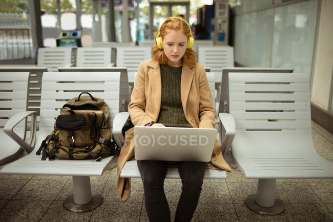 Young woman listing to music while working on laptop at bus stop — Stock Photo