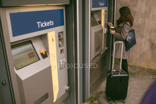 Donna che prende il biglietto dalla macchina alla piattaforma ferroviaria — Foto stock