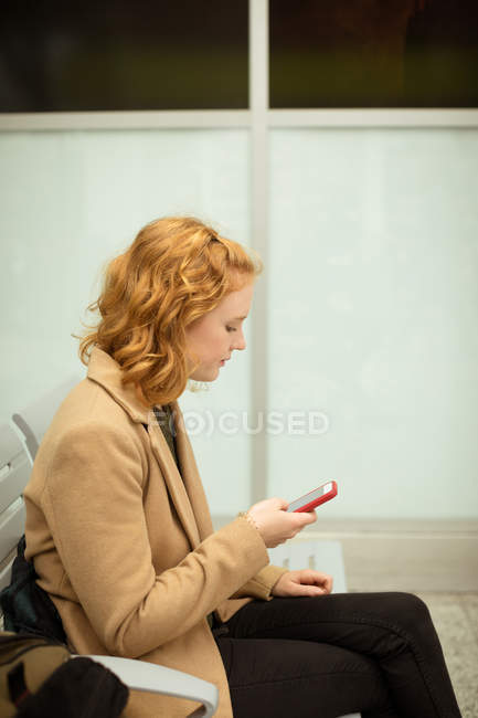 Young woman using mobile phone while travelling in train — Stock Photo