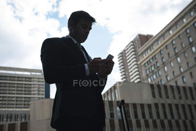 Seitenansicht von Geschäftsmann mit Handy gegen Wolkenkratzer — Stockfoto