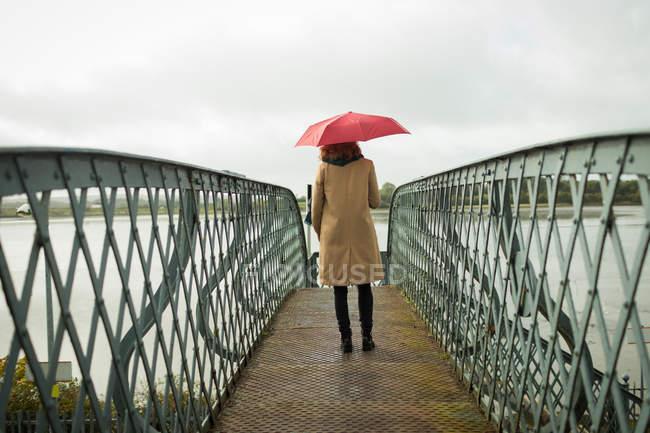 Задній вид на жінку що стояла з парасолькою на залізничному вокзалі — стокове фото