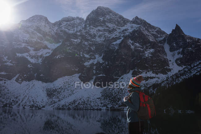 Escursionista donna in piedi con zaino sul lungolago durante l'inverno — Foto stock