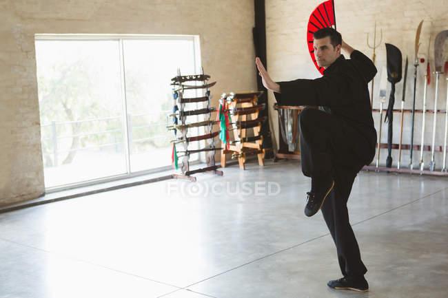 Homem praticando com fã de kung fu em estúdio de fitness . — Fotografia de Stock