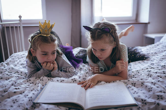 Schwestern lesen ein Buch auf dem Bett im Schlafzimmer — Stockfoto