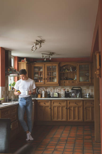 Man using mobile phone and holding cup of coffee in kitchen at home. — Stock Photo
