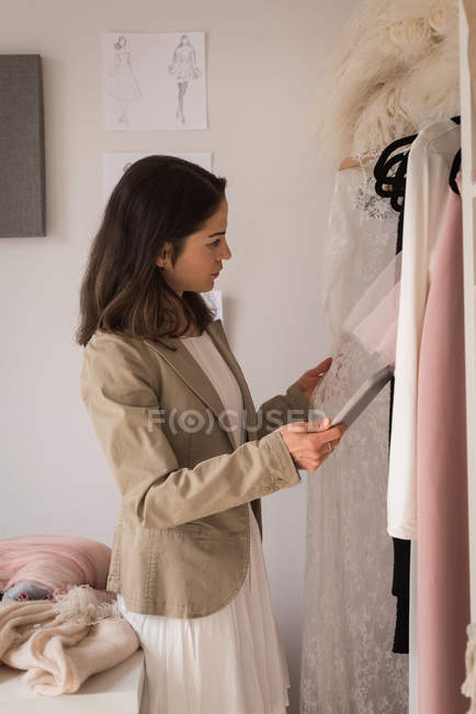 Concentrated fashion designer checking dresses in design studio. — Stock Photo