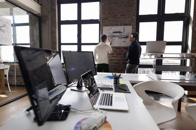 Деловые коллеги обсуждают наброски в офисе . — стоковое фото
