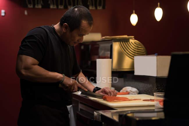 Шеф-повар, филе рыбы в кухне ресторана на разделочную доску — стоковое фото