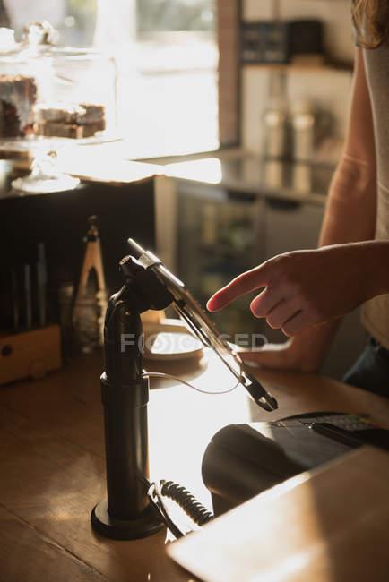 Sección media del camarero teniendo orden de tableta digital en el mostrador de la cafetería - foto de stock