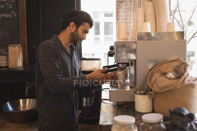 Barista using portafilter while preparing coffee in coffee machine at coffee shop — Stock Photo