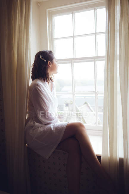 Thoughtful woman looking out of the window at home — Stock Photo