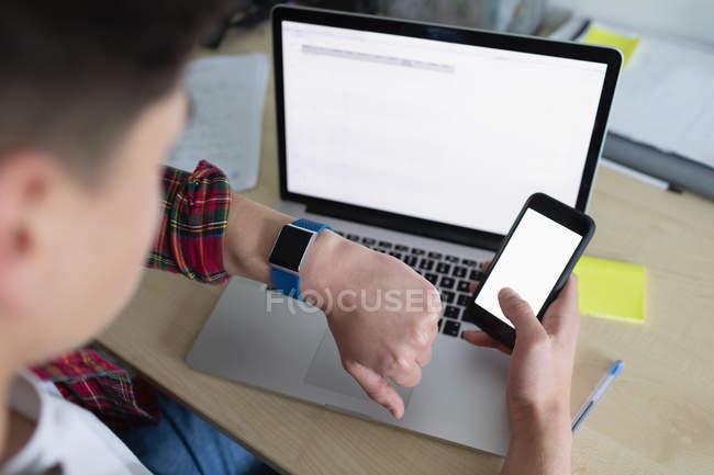 Mann benutzt Handy und Smartwatch per Laptop. — Stockfoto
