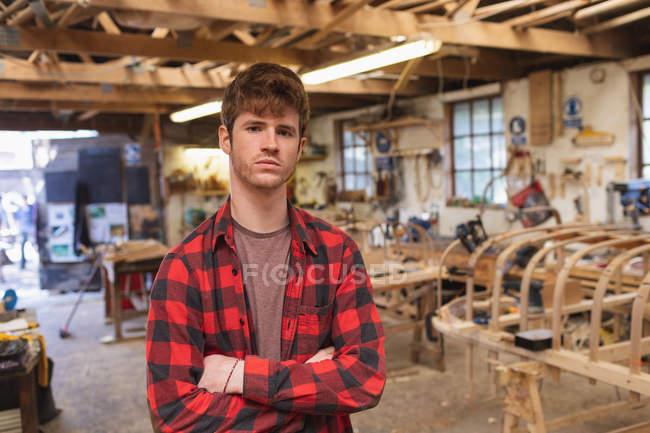 Tischler steht mit verschränkten Armen in Werkstatt — Stockfoto