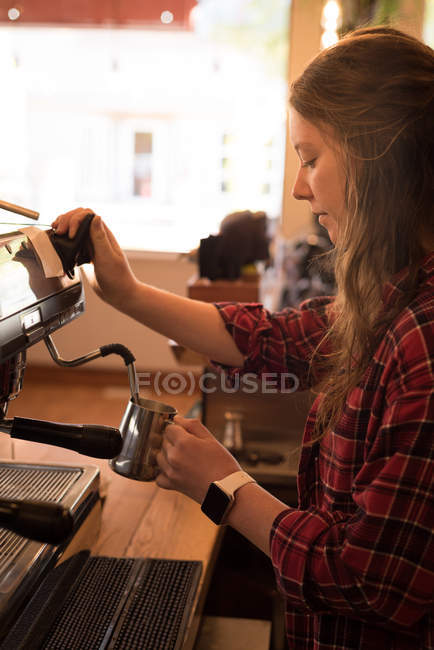 Beautiful woman preparing coffee at counter in cafe — Stock Photo