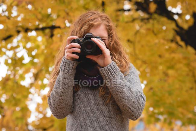 Mujer tomando una foto con cámara digital en el parque de otoño - foto de stock