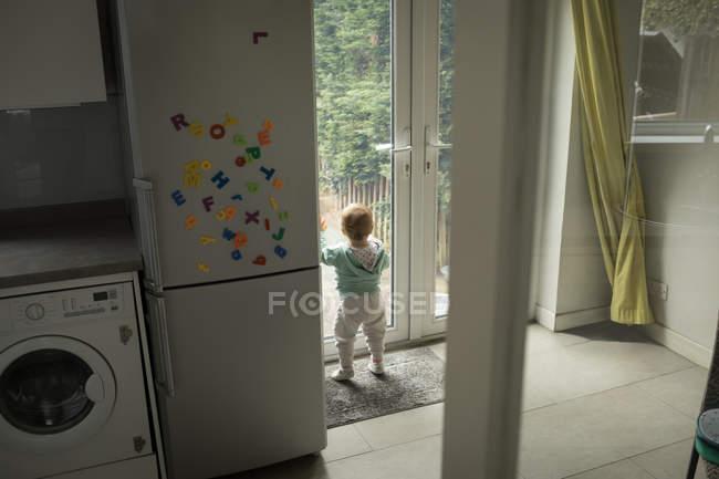 Задній вид дівчинку дивлячись через двері в домашніх умовах — стокове фото
