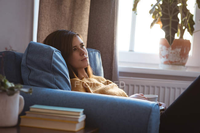 Young woman relaxing on sofa having a coffee during daytime at home — Stock Photo